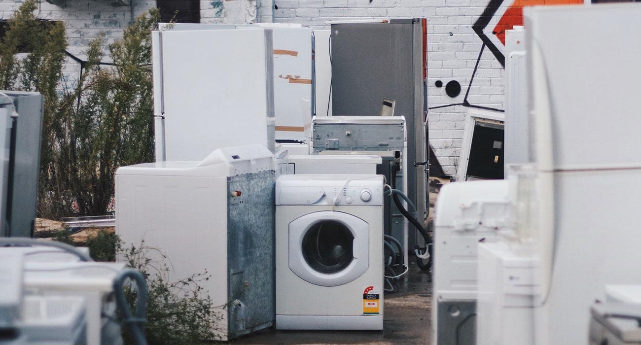 Viel Elektroschrott auf einem Platz, im Mittelpunkt steht eine Waschmaschine