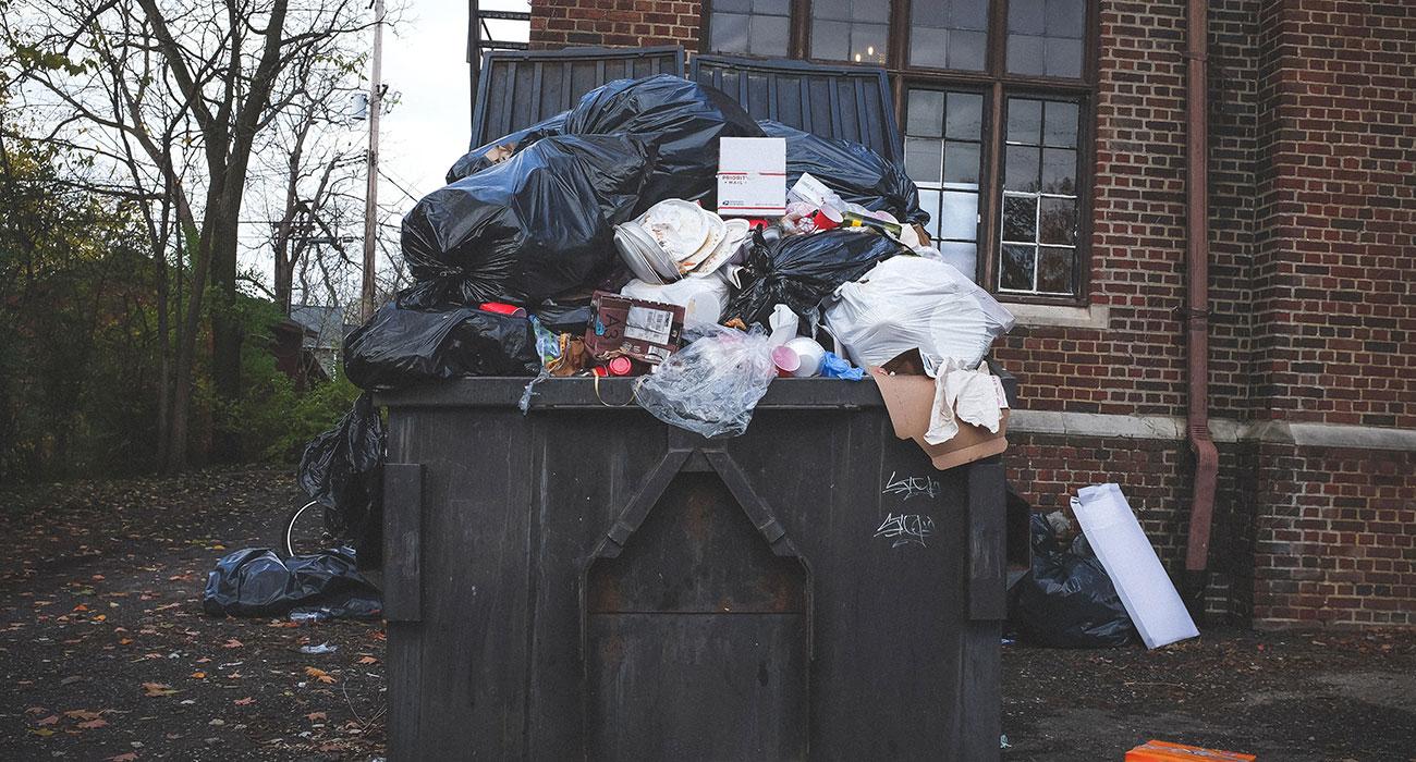 Große Industriemülltonne quillt wegen viel Müll über
