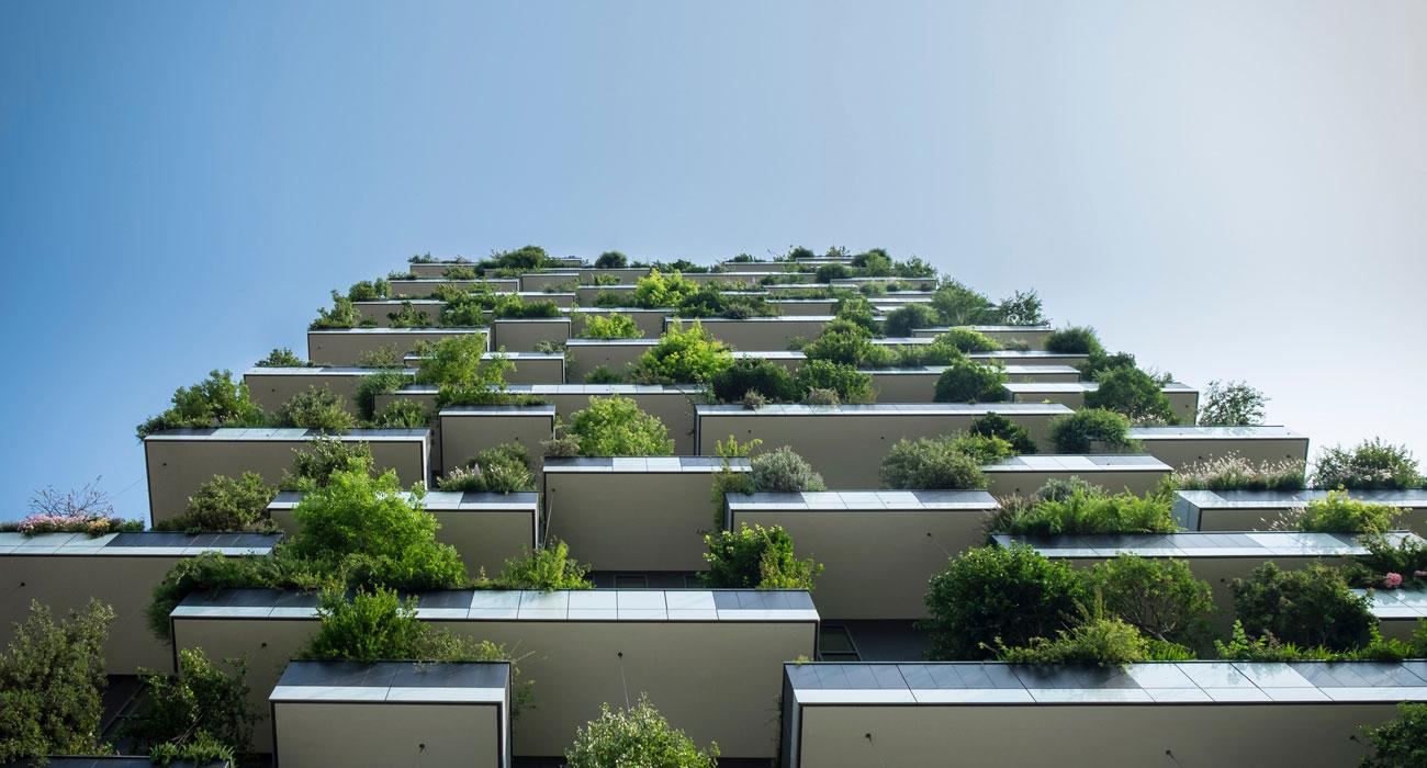 Hochhaus mit vielen Pflanzen auf Balkonen von unten nach oben fotografiert