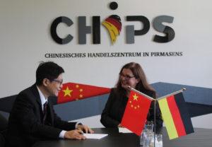 Eine Frau und ein mann am Tisch mit chinesischer und deutscher Flagge